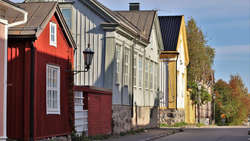 Kesäinen katunäkymä Neristanista. Kuvan vasemmassa reunassa on vanhoja puutaloja, lähimpänä punainen harjakattoinen talo, jossa valkoiset ikkunanpielet. Talon seinästä lähtee metallinen varsi, jonka päässä on vanha katulyhty. Talojen edessä kulkee asfaltoitu katu.