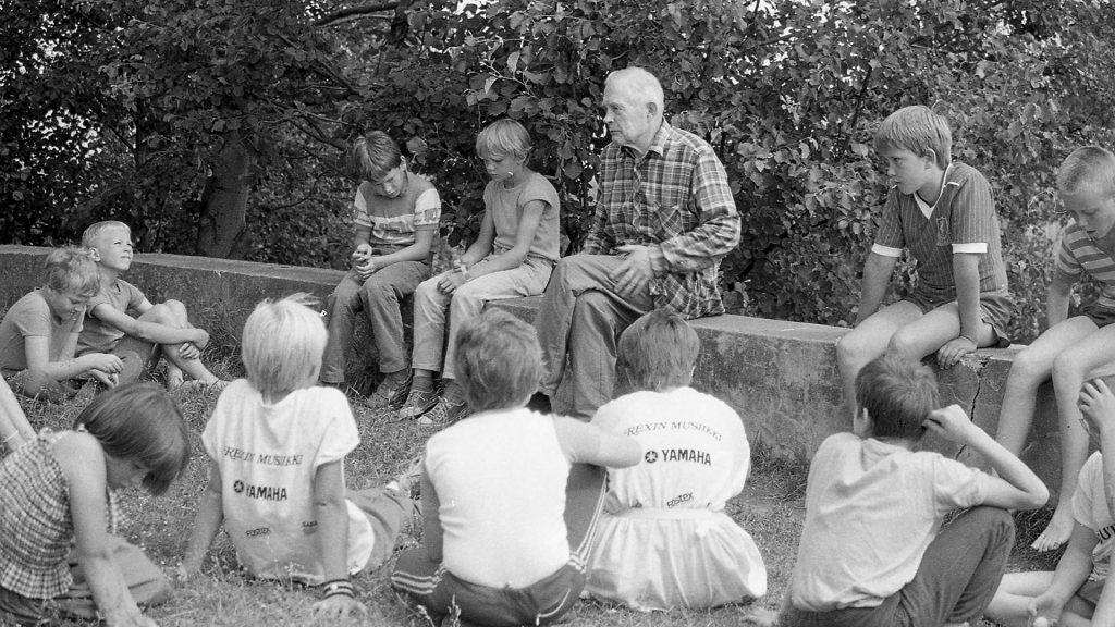 Salkio ja neljä lasta istuvat kivimuurilla. Joukko muita lapsia istuu heidän edessään nurmikolla.
