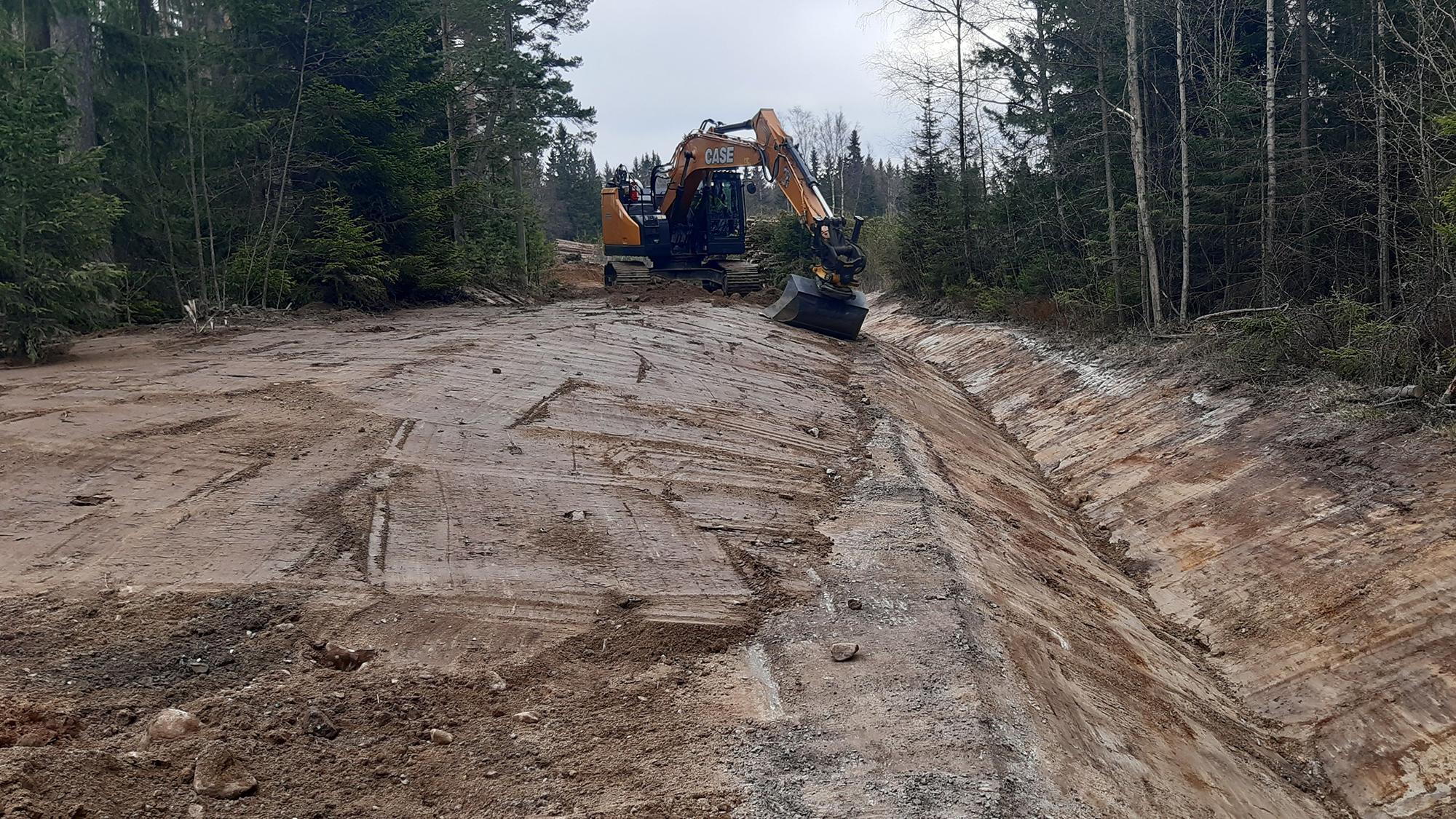 Kaivinkone kaivaa ojaa valmistuvalle tielle