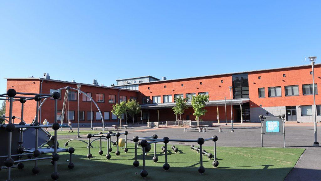 Lucina Hagmanin koulurakennus ja piha-alue kesäpäivänä.