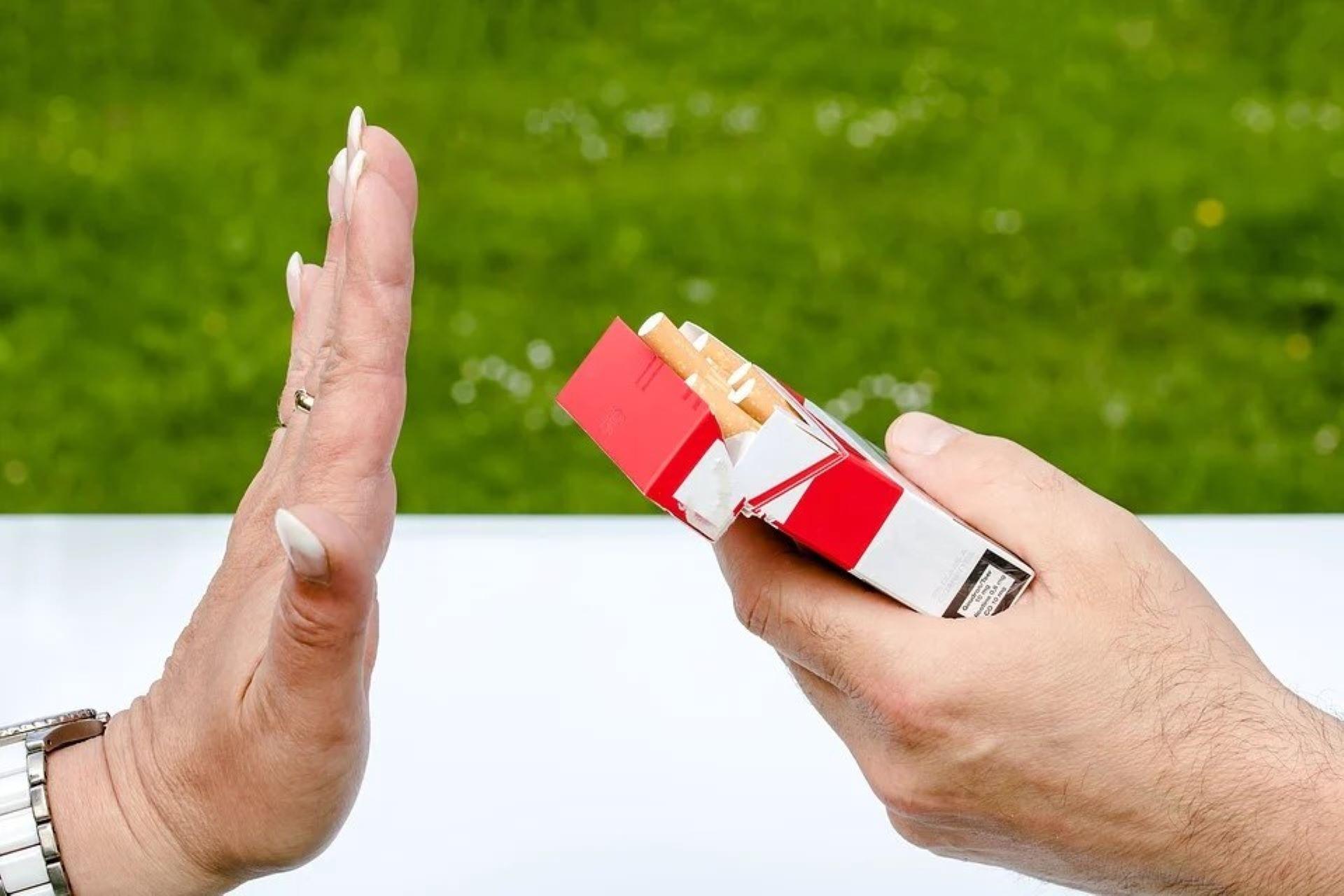 Naisen käsi on torjuvasti pystyssä miehen käden tarjoamaa tupakka-askia kohden.