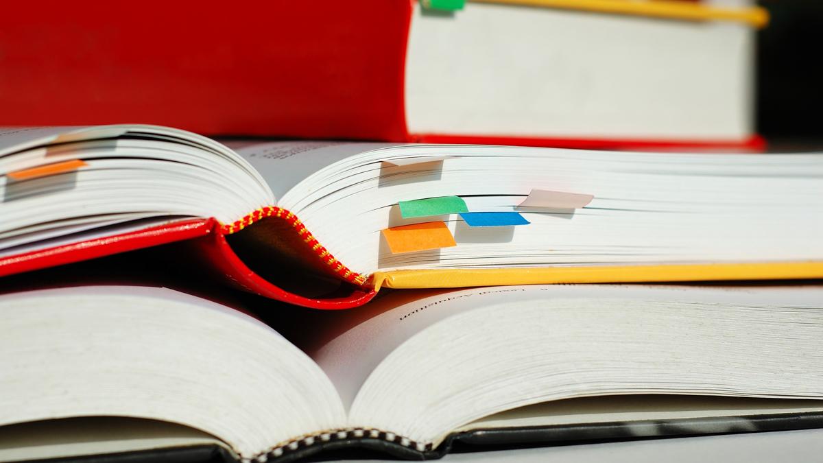 Tre öppna böcker med flera bokmärken