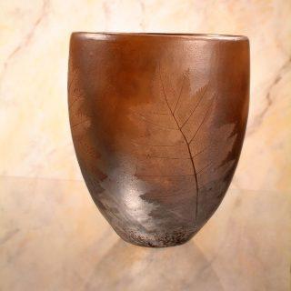 Ruskea, kiiltävä saviastia, jossa on painettuna kaunis lehtikuviointi.