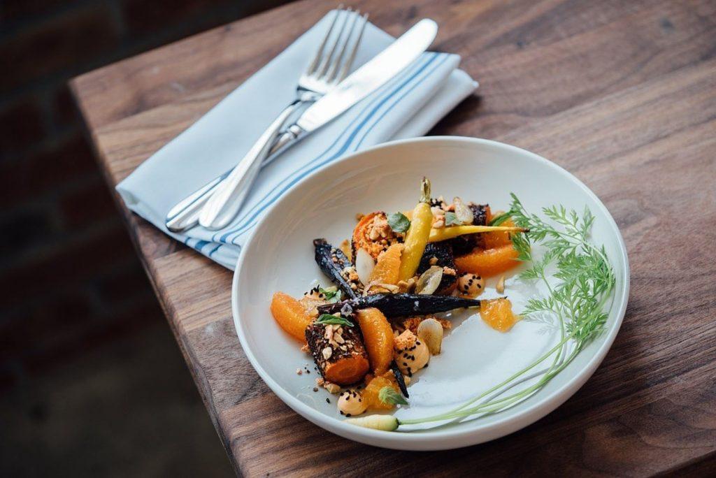 Pöydällä on lautanen, jolla on värikäs ruoka-annos. Lautasen vieressä on aterimet lautasliinan päällä.