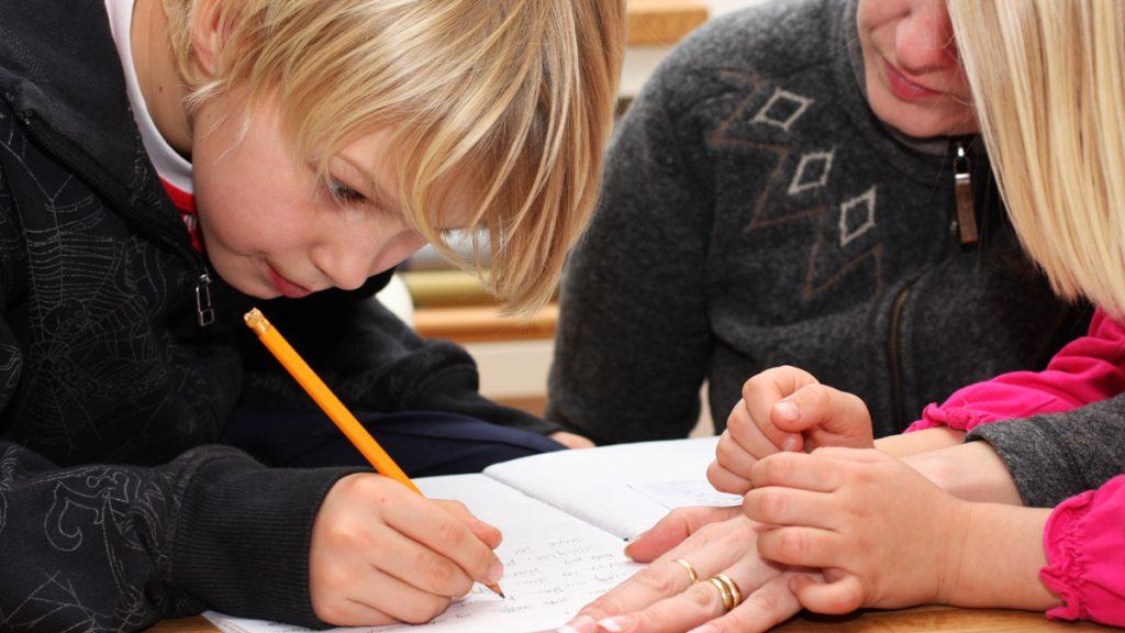 Poika kirjoittaa käsin, aikuinen ohjaa vieressä