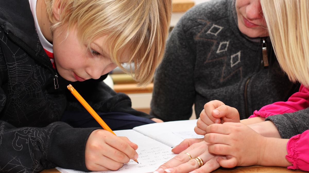 En pojke skriver för hand, en lärare handleder bredvid