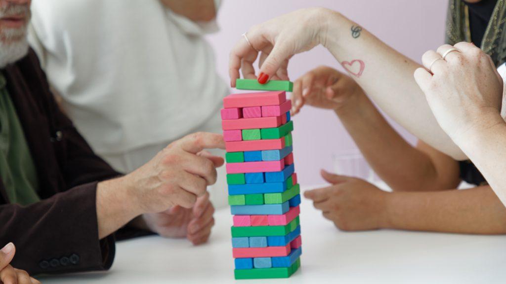 En grupp människor bygger ett blocktorn på bordet