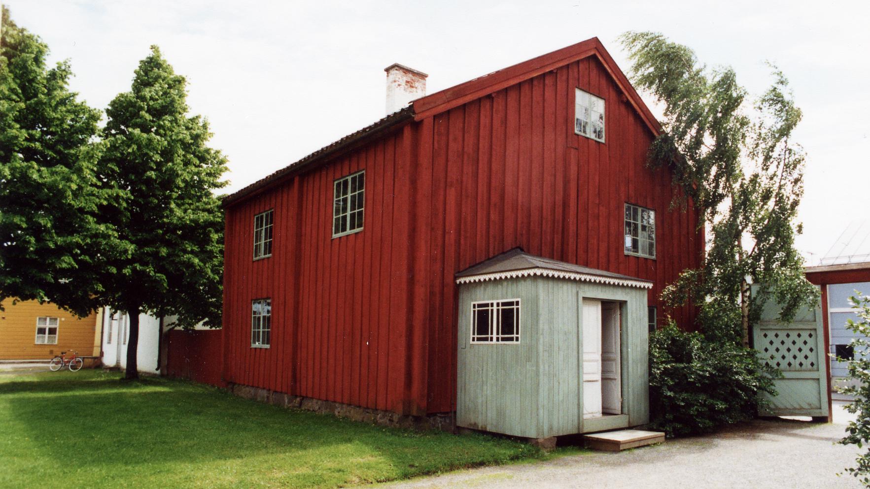 Punainen, puinen vanha rakennus kesällä kuvattuna.