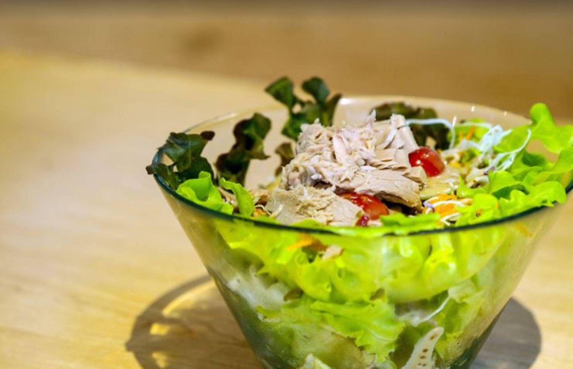 Värikäs salaattiannos lasikulhossa pöydällä.
