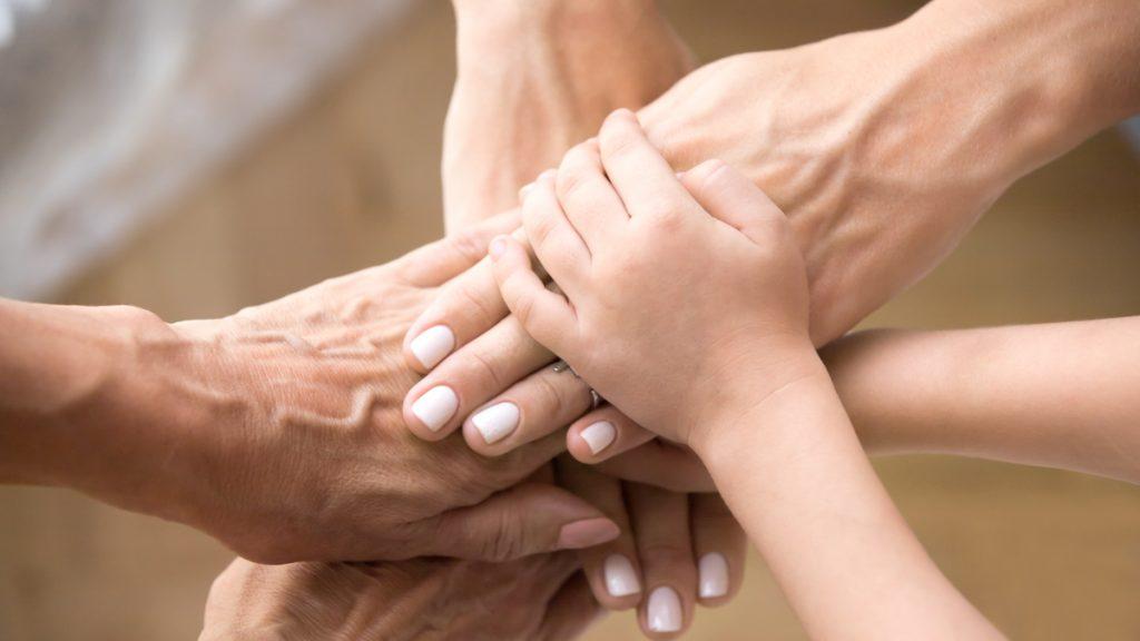 De unga och de gamla handerna tillsammansa.