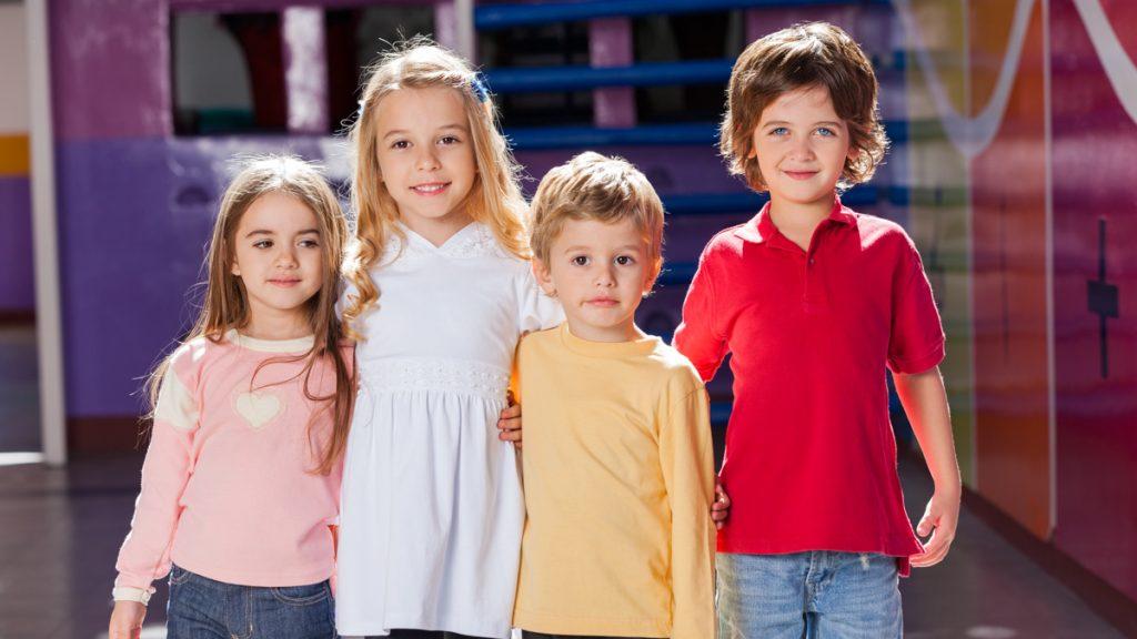 Neljä lasta vierekkäin ulkona