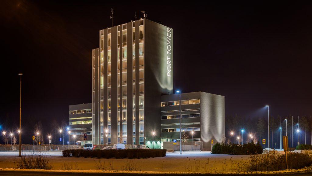 Tummaa iltataivasta vasten kohoava valaistu toimistorakennus Port Tower, jonka ympärillä lukuisia katulamppuja piha-aluetta valaisemassa. Piha on lumen peitossa.