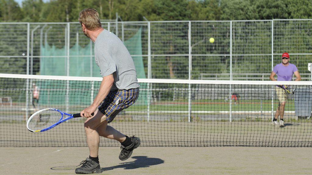 Kaksi miestä pelaamassa tennistä ulkokentällä. Lähempänä, selin kameraan olevalla miehellä on kädessään sininen maila ja yllään ruudulliset shortsit sekä harmaa t-paita. Kauempana, verkon toisella puolella olevalla miehellä on yllään lila t-paita sekä päässään lippalakki ja aurinkolasit. Verkon yläpuolella lentää keltainen tennispallo.