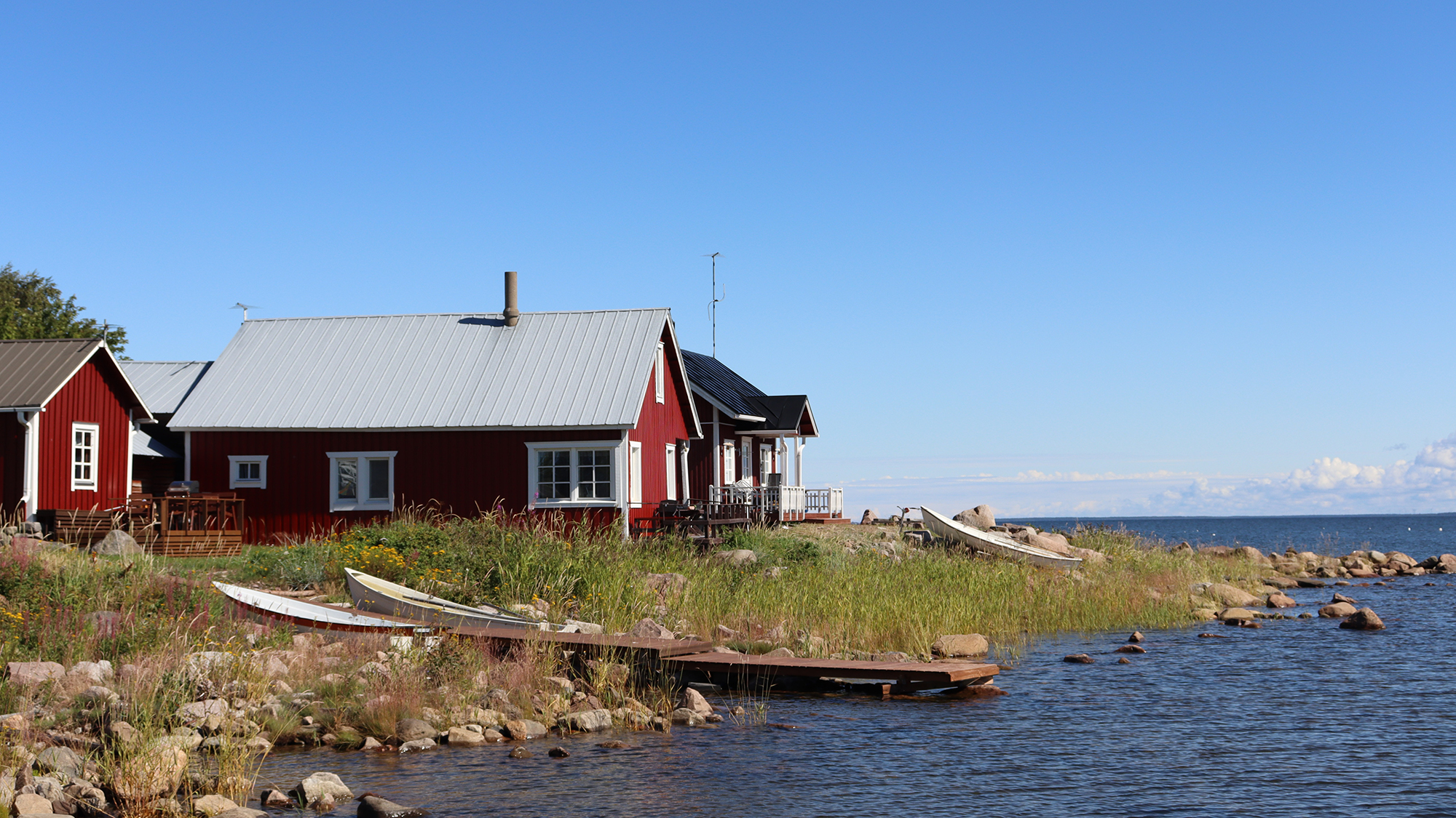Ohtakarin kivien ja pitkän ruohon peittämä rantaviiva. Kuvan etualalla on mereen työntyvä puinen laituri sekä sen viereen maalle nostetut kaksi venettä. Taustalla näkyy punaisia, harjakattoisia rakennuksia sekä sininen, lähes pilvetön taivas. Kuvan oikeassa reunassa on tummansininen meri.