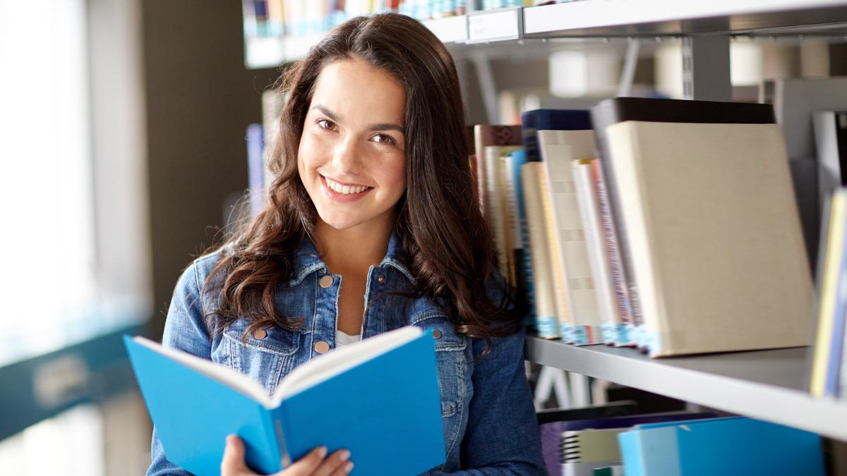 Tyttö seisoo lukemassa kirjahyllyn edessä