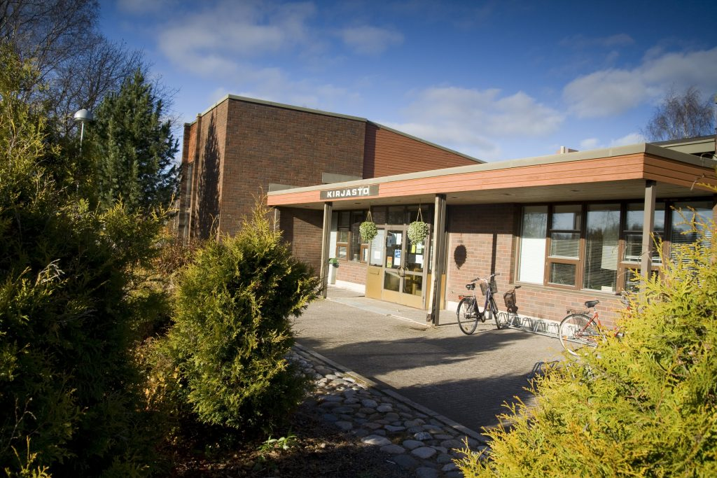 Kälviän kirjaston punatiilinen rakennus, edessä istutuksia ja kaksi polkupyörää