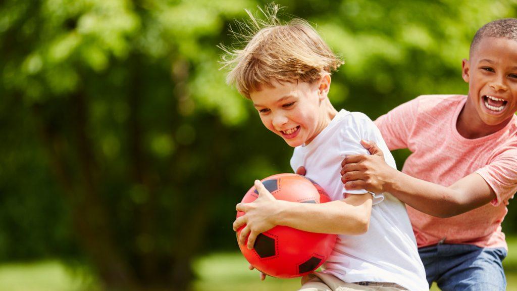 Kaksi poikaa leikkii pallolla