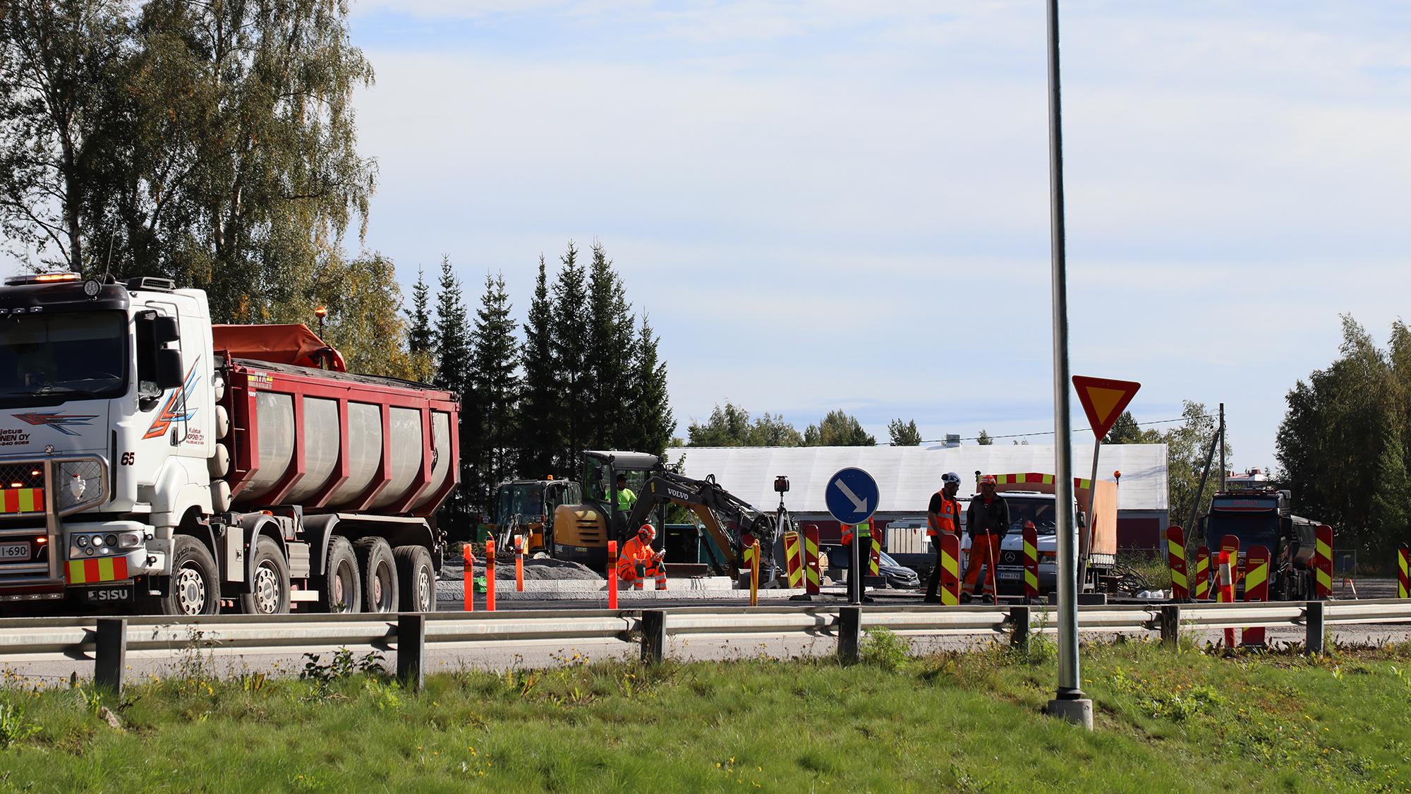 Halkokarin liikenneympyrän rakennustyömaa kesällä. Kuvan vasemmassa laidassa on tien varteen pysäköity kuorma-auto ja sen takana työmaa, jossa työntekijöitä ja työntekoon tarvittavaa kalustoa.