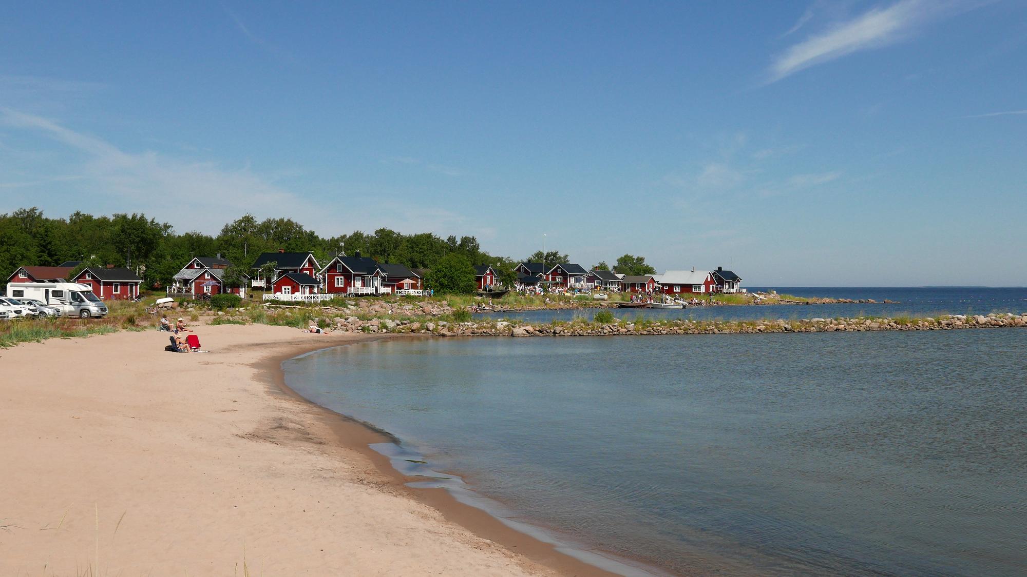 Näkymä Vattajan uimarannasta. Kuvan vasemmassa reunassa on hiekkaranta ja oikeassa reunassa meri. Taustalla näkyy mereen työntyvä kivikkoinen aallonmurtaja sekä pitkin rantaa olevia harjakattoisia mökkejä sekä muutama auto.