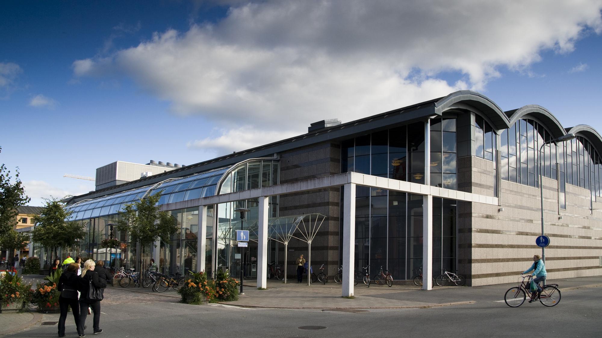 Kokkolan kaupunginkirjasto etuviistosta kuvattuna. Kirjastolla on useista kaarevista elementeistä tehty katto sekä harmaasta kivestä ja suurista lasipinnoista tehdyt seinärakenteet. Kirjaston edestä kulkee Tehtaankatu, jossa liikkuu jalankulkijoita ja pyöräilijöitä. Kadulla on myös runsaasti istutuksia. Kirjaston yläpuolella näkyy sininen taivas, jossa isoja pilviä.