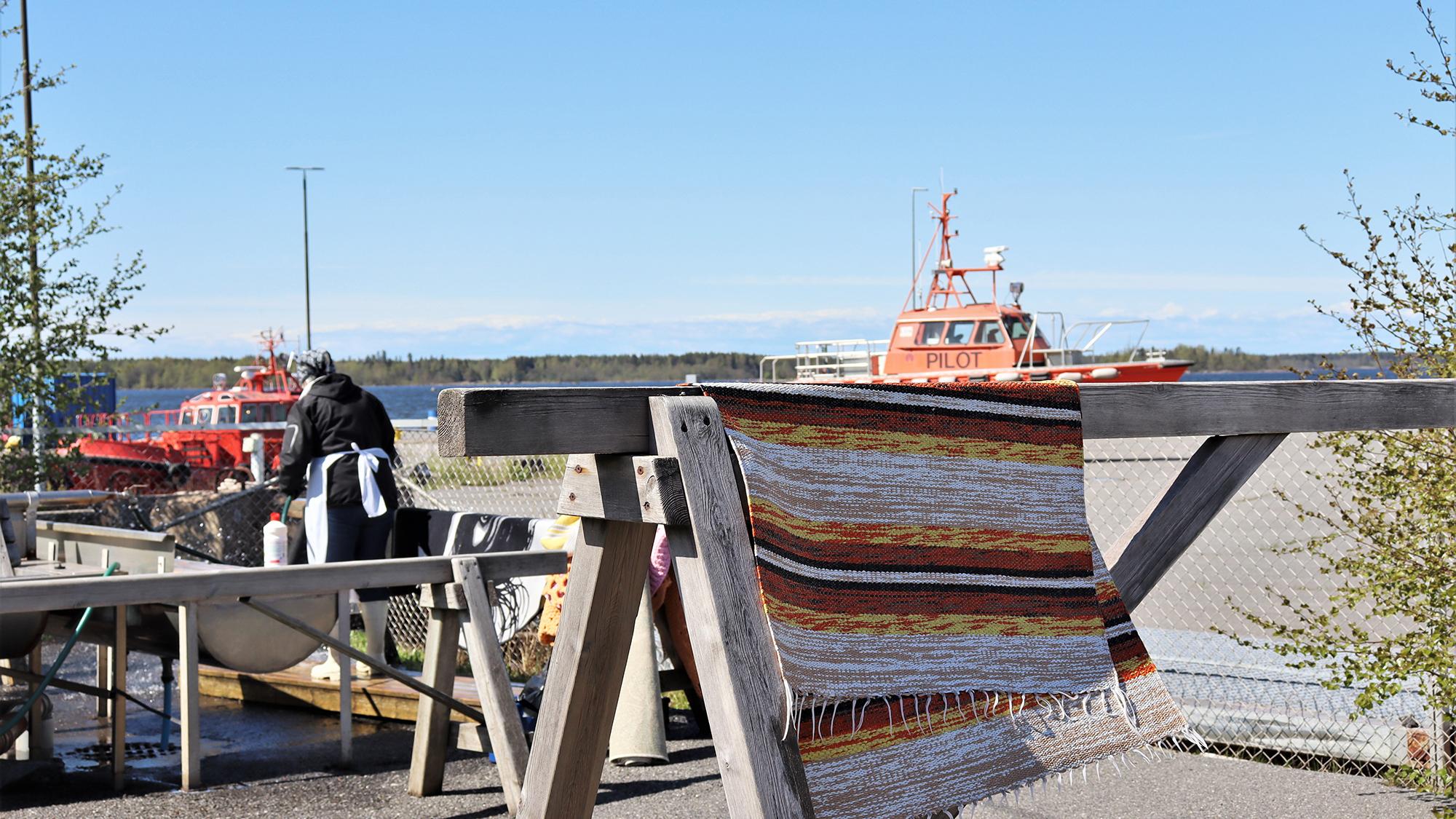 Raidallinen matto kuivumassa puisella telineellä. Taustalla näkyy mattoja pesemässä oleva nainen sekä meri ja siellä liikkuva moottorivene.