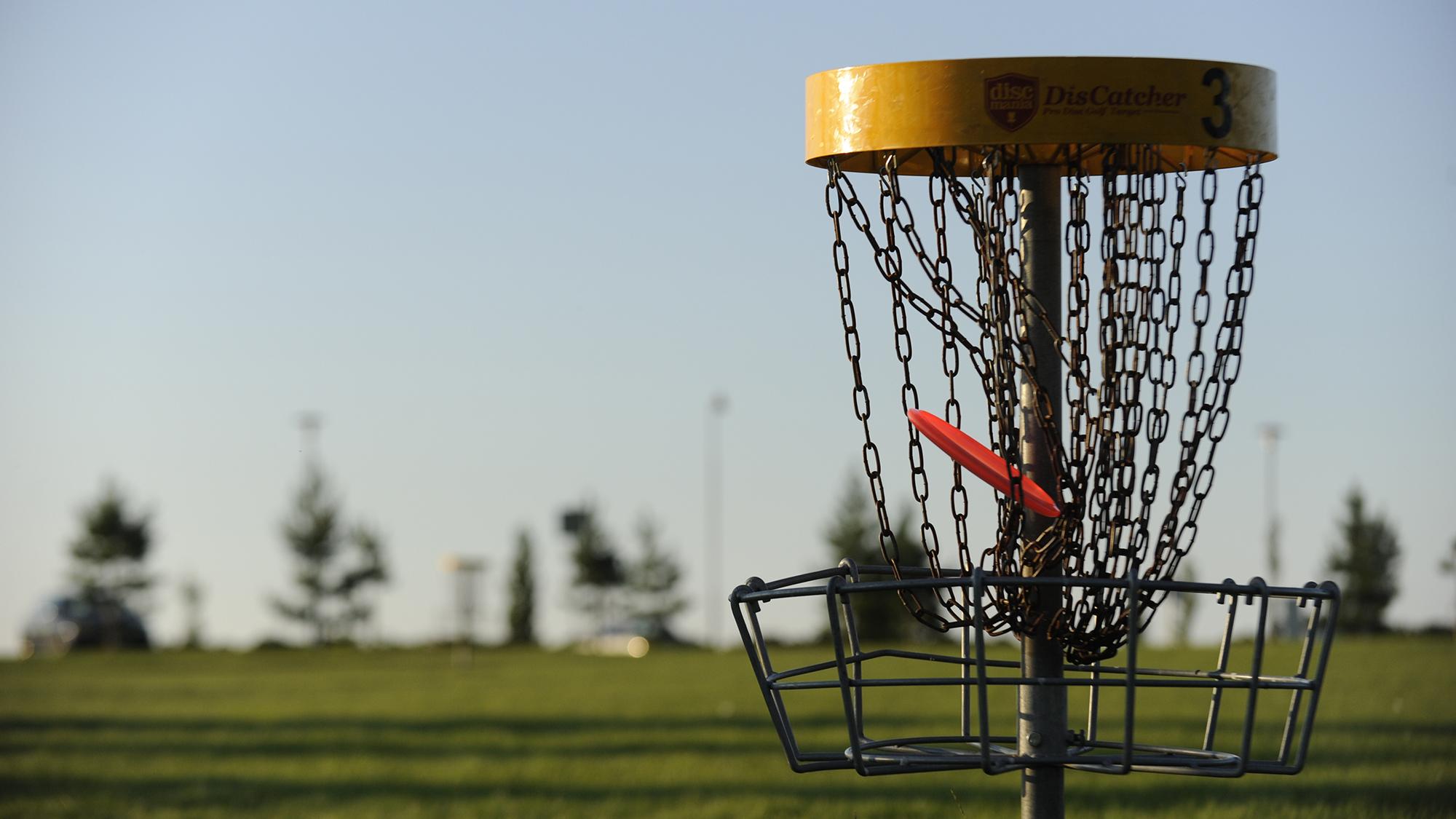 Frisbeegolfkori lähietäisyydeltä kuvattuna. Keltaisella reunalla varustetun korin ketjuihin on juuri lentänyt punainen frisbee.