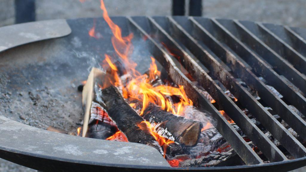 Musta tulisija, jossa palavia, tummaksi hiiltyneitä polttopuita.