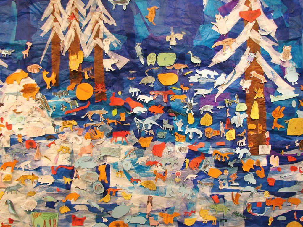 Lasten piirtämiä eläimiä kiinnitettynä silkkipaperista tehdylle, talvista metsää kuvaavalle taustalle.