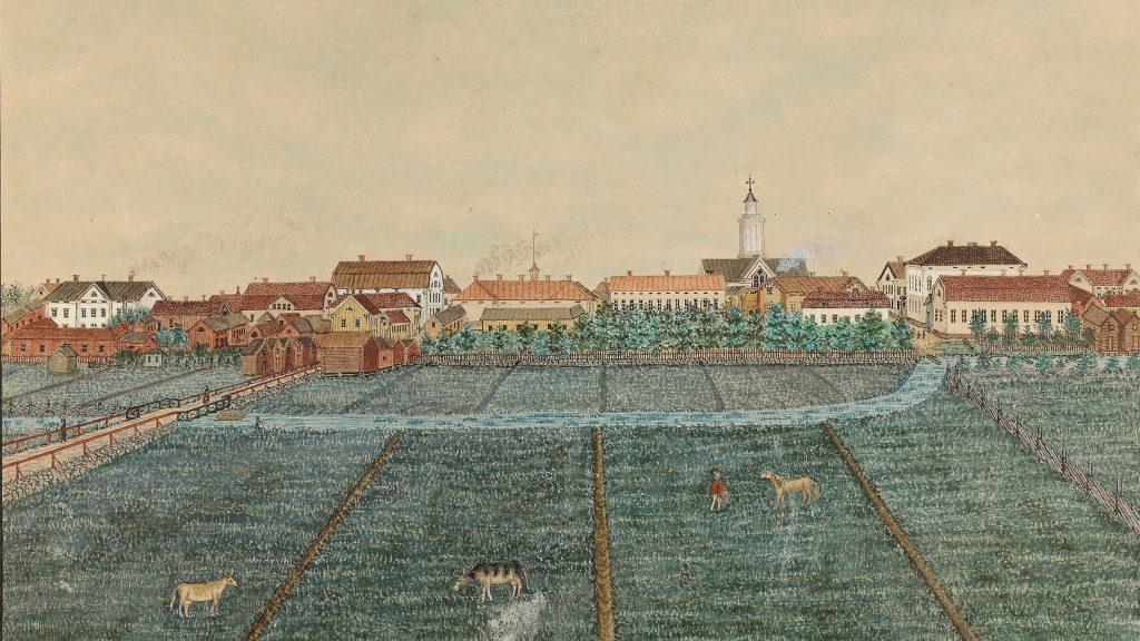 Kuvaus vanhasta kaupungista rakennuksineen, etualalla näkyy niittyä ja lehmiä.