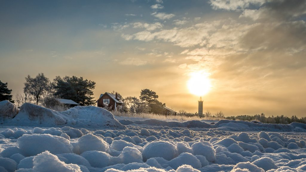 Aurinko paistaa Harrbådan majakan takaa talvella.