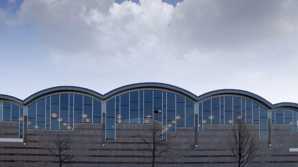 Kokkolan kaupunginkirjaston kaareva kattorakenne ja sen alapuolella olevat ikkunat, joiden takaa loistavat kirjaston sisällä olevat kattolamput. Ikkunoiden alapuolella on harmaa kivinen seinä, jonka edessä on kolme lehdetöntä puuta. Kirjaston yläpuolella on pilvinen taivas.