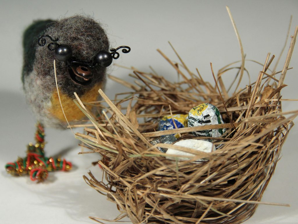 Erilaisista materiaaleista rakennettu lintu, linnunpesä ja munia.