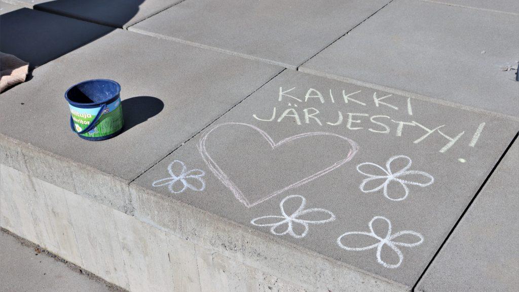 """Laattoihin on kirjoitettu katuliiduilla """"Kaikki järjestyy"""" sekä piirretty kukkia ja sydän."""