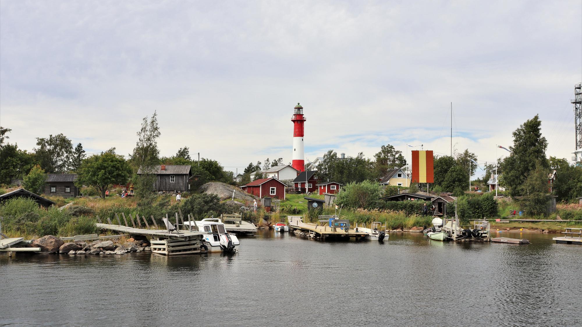 Mereltä otettu kuva Tankarin venesatamasta. Taustalla näkyy saarella olevia puumökkejä sekä Tankarin punavalkoinen majakka.