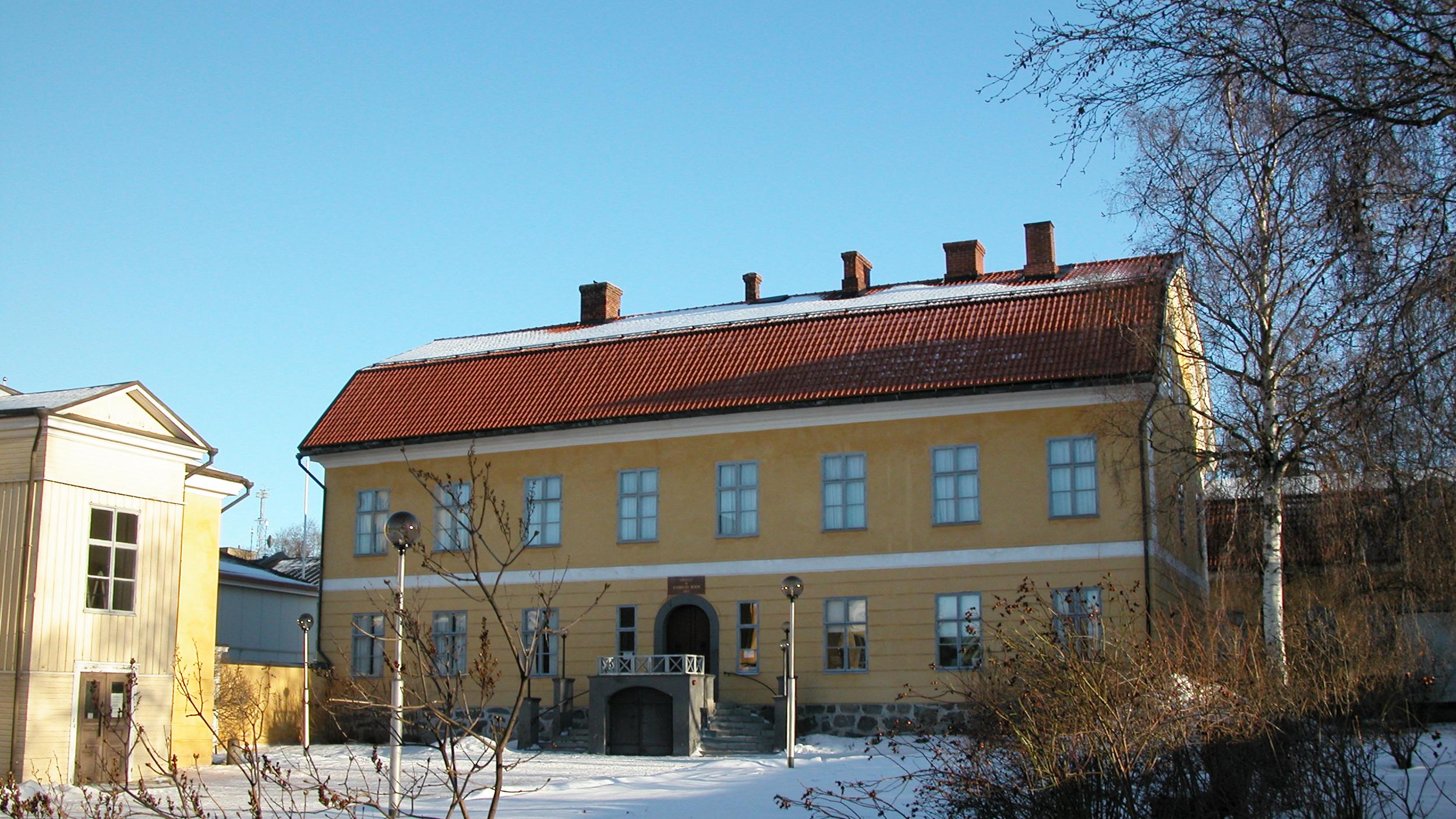 Suuri, keltainen kivirakennus on kuvattu aurinkoisena talvipäivänä.