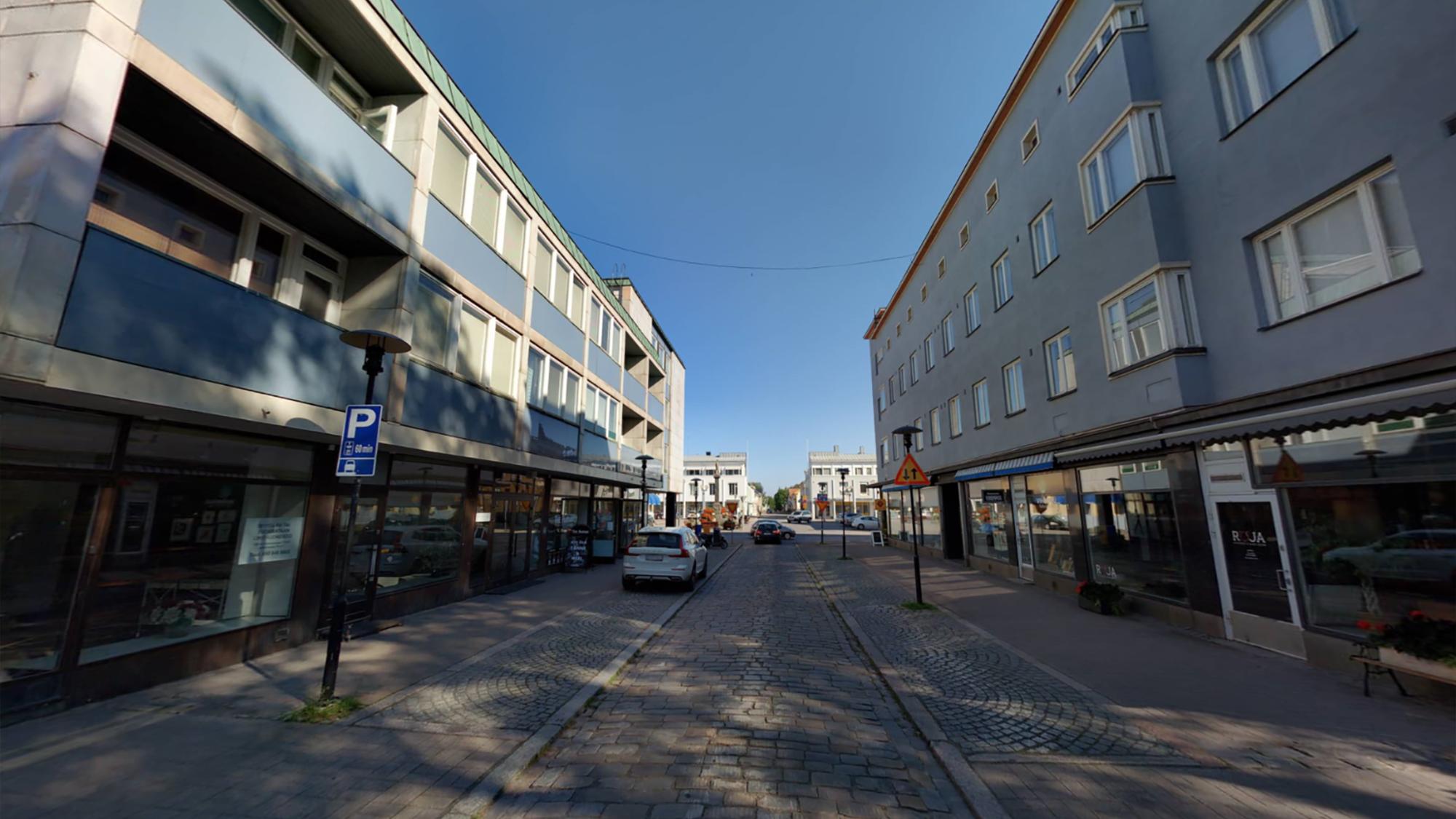 Näkymä Isokadulta, jossa molemmilla puolin katua matalia kerrostaloja. Kerrostalojen katutasossa on liiketiloja ja ylemmissä kerroksissa asuntoja. Kadun keskiosa on tehty mukulakivistä ja sen reunamilla on pysäköintipaikkoja kadun molemmin puolin. Taustalla etäisenä näkyy Mannerheiminaukio.