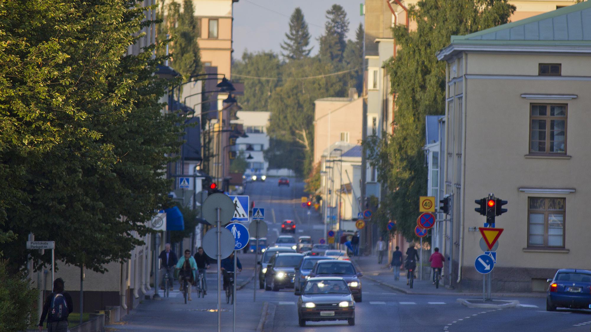 Katunäkymä Torikadulta. Kadun molemmin puolin on korkeita rakennuksia ja kadulla paljon autoja sekä pyöräilijöitä.