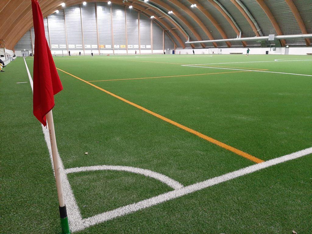 Kuvassa näkyy avara jalkapallohalli, kulmalippu ja kenttämerkinnät