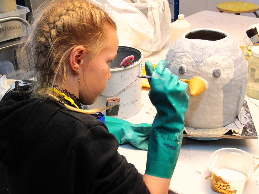 Tyttö maalaa keramiikkateosta