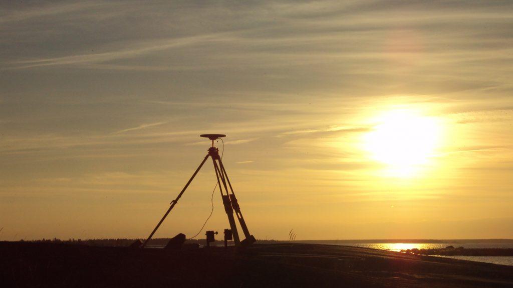 Tukipistemittausta rannalla. Hämärtyvässä illassa otettu kuva aakealle rannalle pystytetystä GPS-paikantimesta. Taustalla siintää meri ja taivaalla pilviharson lomassa laskeva aurinko.