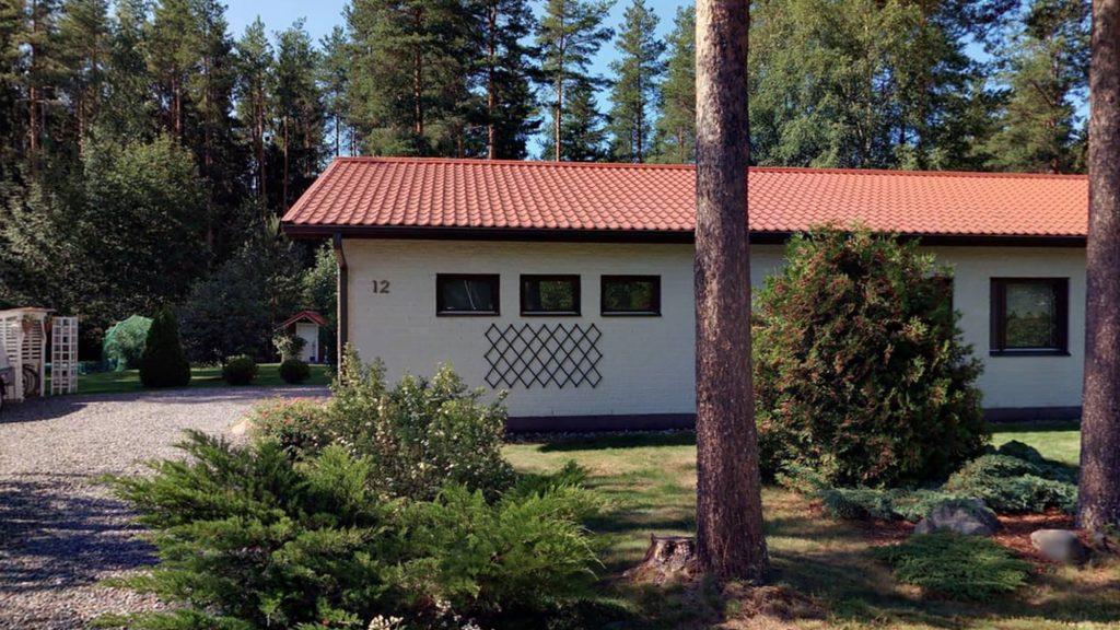 Valkoinen talo, jossa on punertava katto. Talon seinässä on osoitenumero kultaisilla numeroilla. Etualalla näkyy pihaa, jossa on pari puuta sekä erilaisia pensaita.
