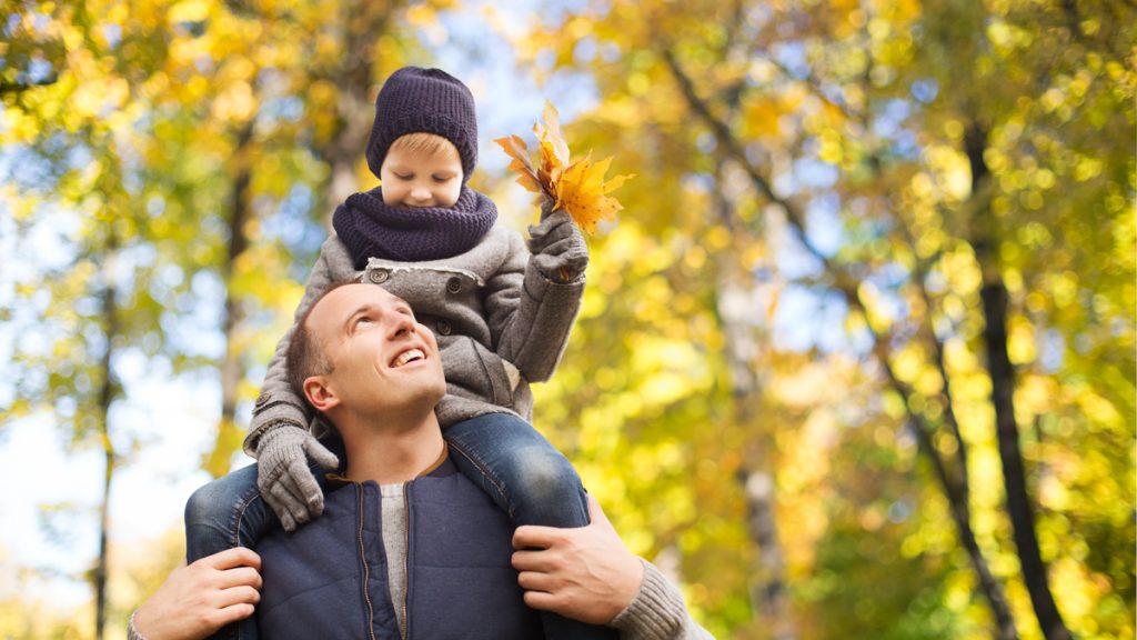 Isä kantaa lasta olkapäillään syksyisessä maisemassa.
