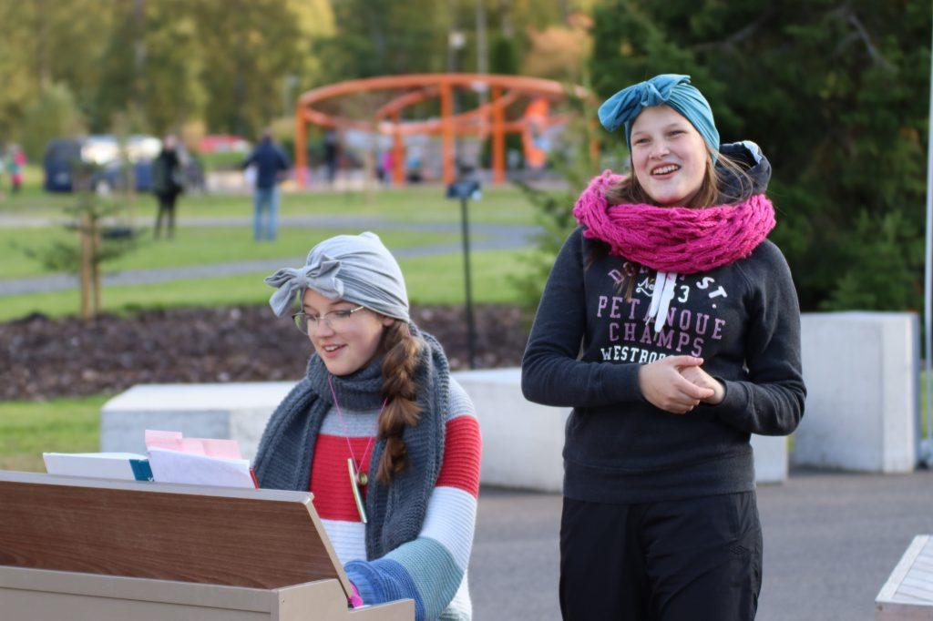 En flicka spelar piano och en flicka sjunger i parken.