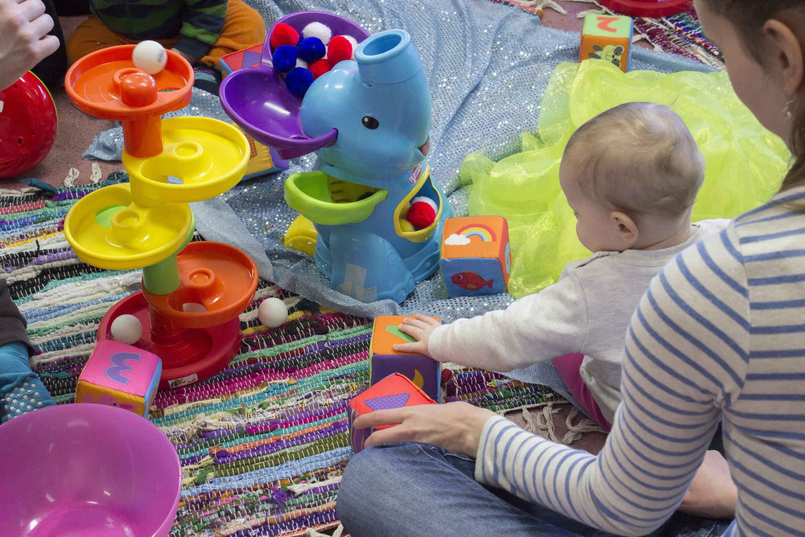 Vauva tutkimassa värikkäistä materiaaleja