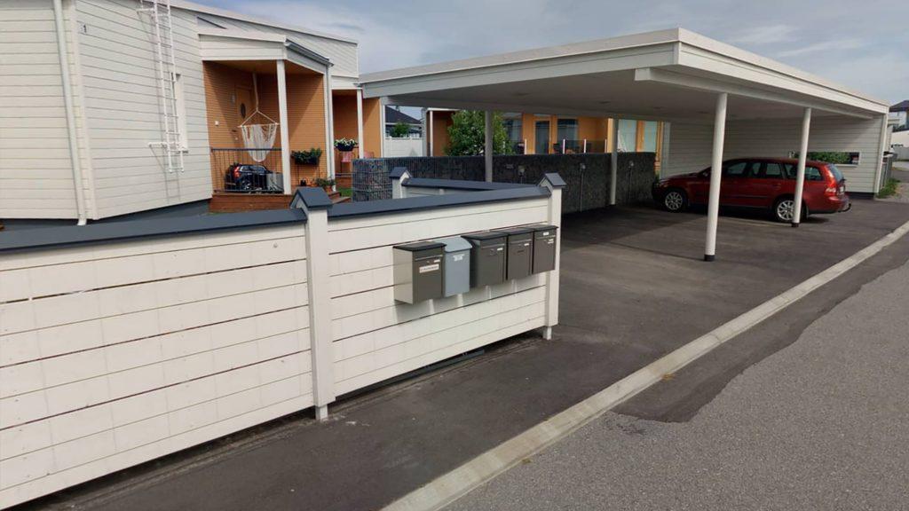 Postilaatikkorivi valko-sinisessä aidassa Asuntomessualueella. Aidan takana näkyy valkoista rakennusta, jonka kuistit on maalattu oransseiksi. Oikealla on oranssi farmariauto valkoisen autokatoksen alla.