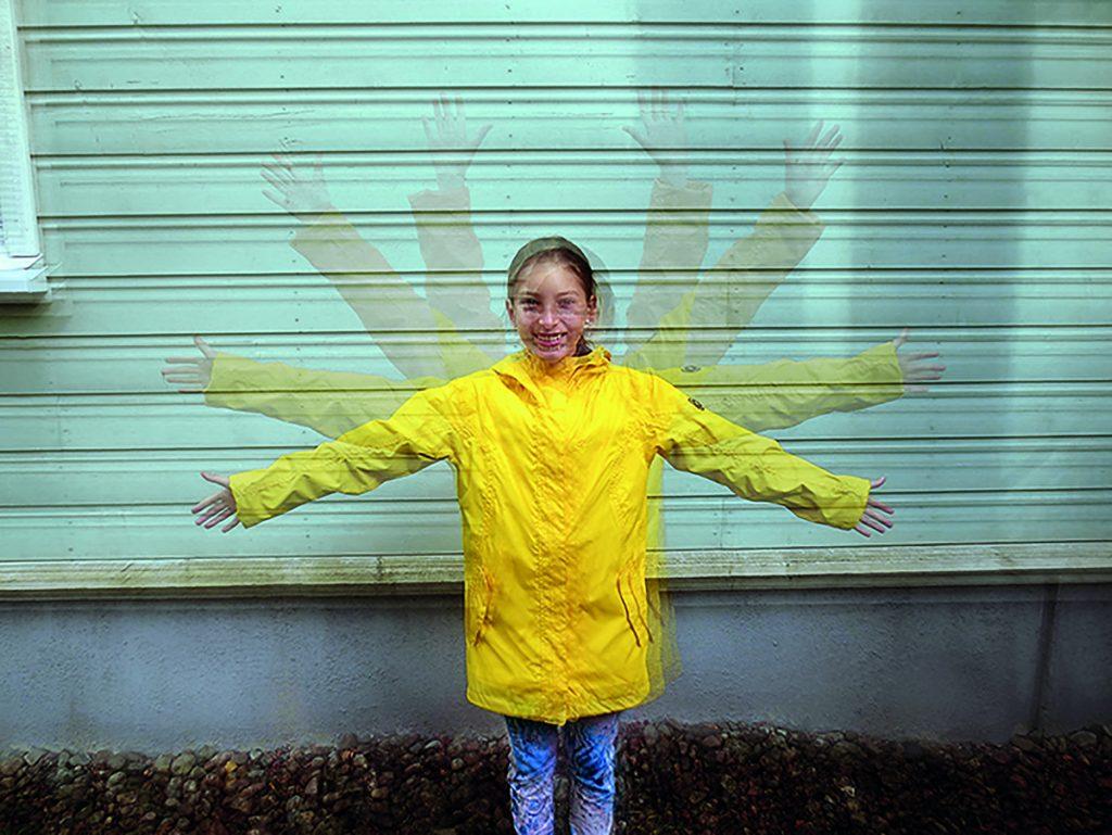 Tyttö keltaisessa takissa heiluttaa käsiä