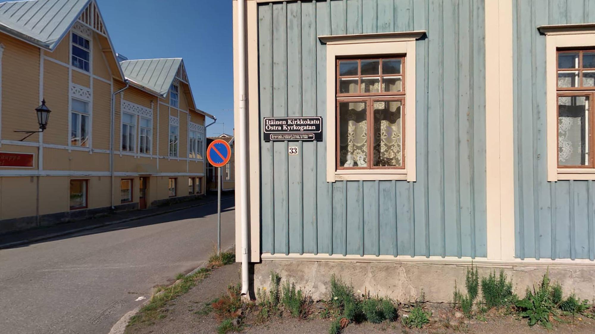 Sinisen talon julkisivu Vanhakaupunki Neristanissa. Talon seinässä on osoitenimi- ja numerokyltti. Vasemmalla näkyy keltaisen talon julkisivua.
