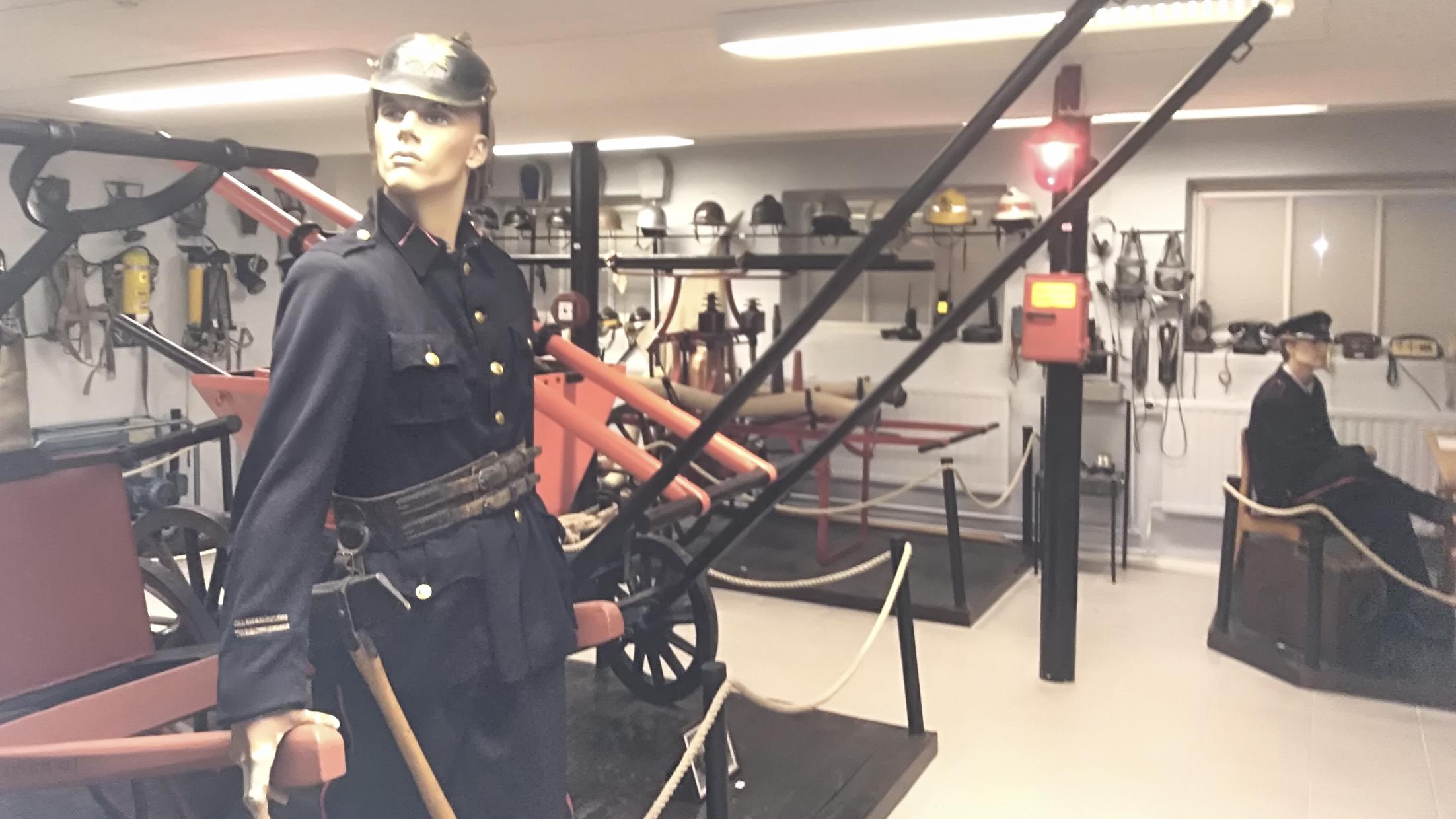 Interiööri, jossa vanhoja palotarvikkeita ja palomiehiksi puettuja mallinukkeja.