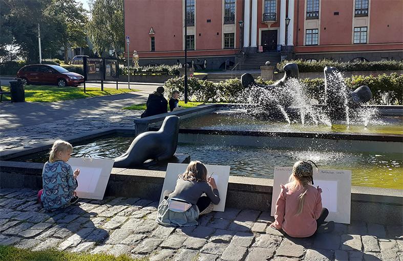 Lapsia piirtämässä ulkona