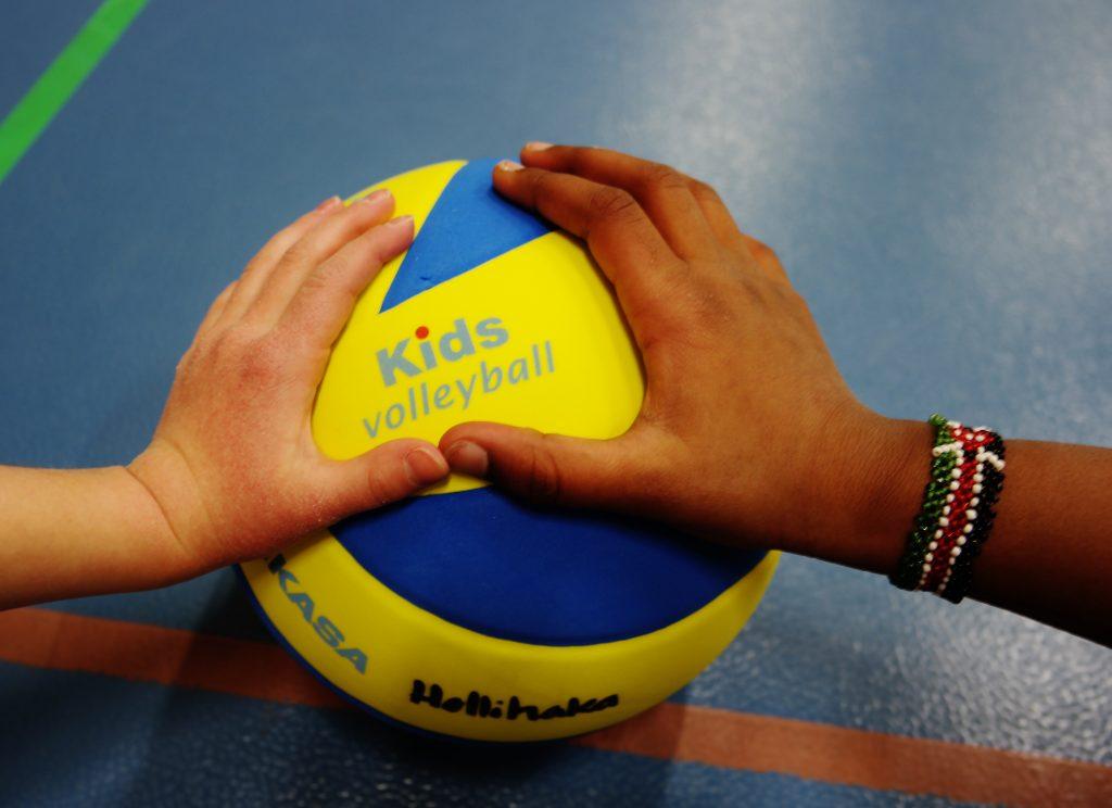 Kuvassa kahden henkilön kädet ja lentopallo